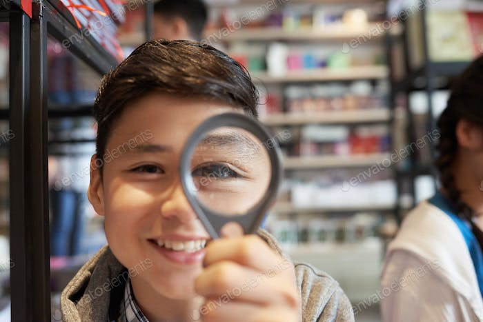 Boy with magnifier in library smiling