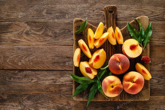 Reife Pfirsiche mit Blättern auf Holzbrett, Draufsicht