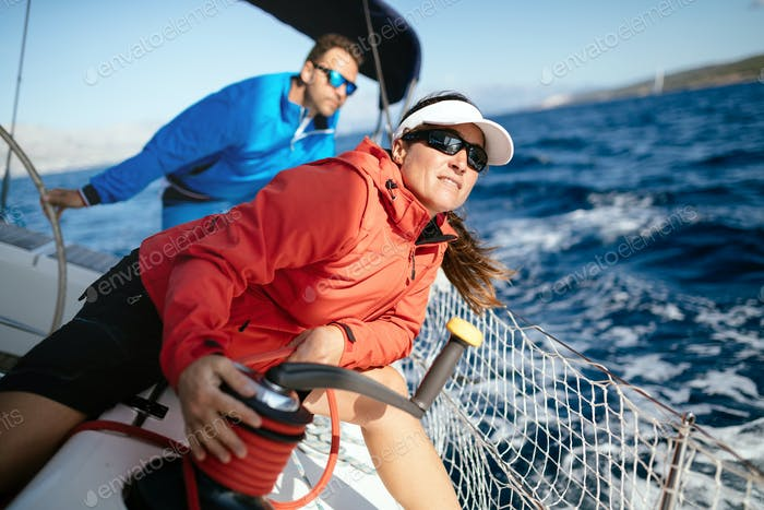 Attractive strong woman sailing with her boat
