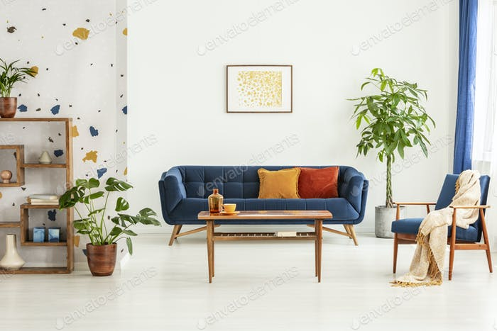 Poster above blue settee in white apartment interior with armcha