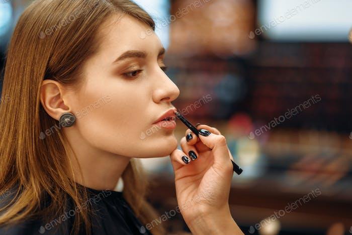 Visagiste and female client in makeup shop