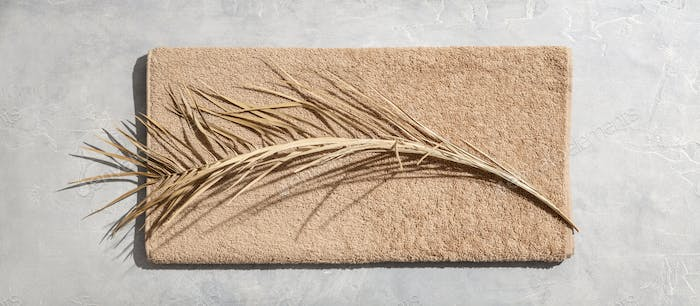 Dried leaf of palm and towel on concrete background