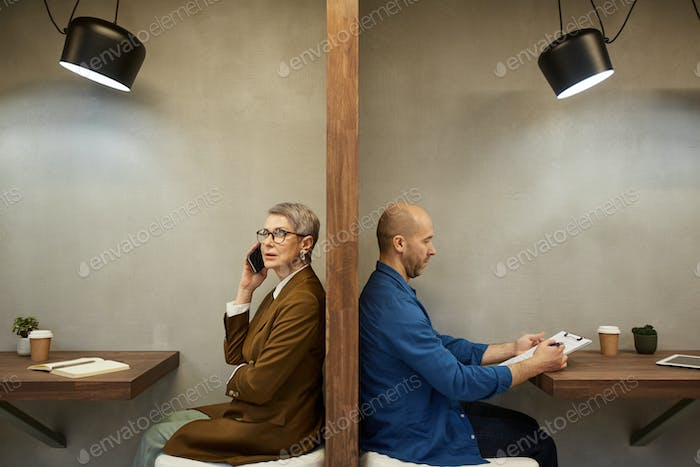 Business People Separated by Wall in Cafe