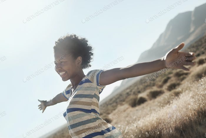 A girl with arms outstretched in a gesture of freedom and excitement, leaning into the breeze.