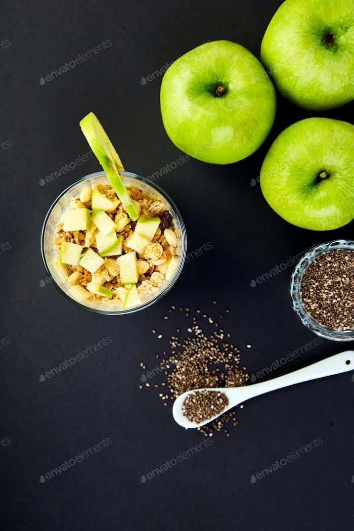 Gesunder Chia-Pudding mit Äpfeln und Müsli im Glas.