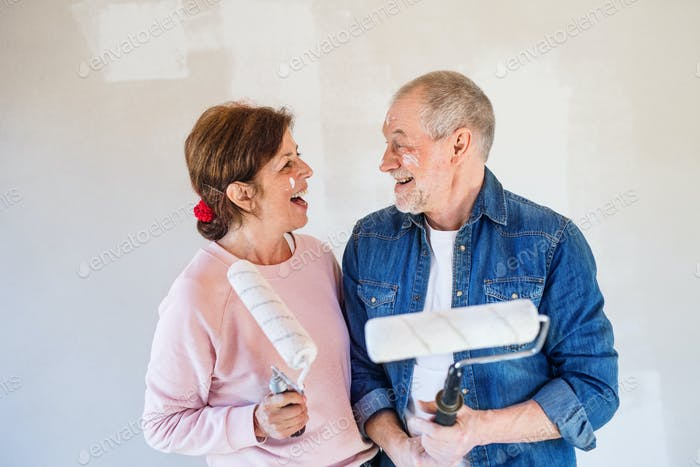 Senior couple painting walls in new home, having fun. Relocation concept
