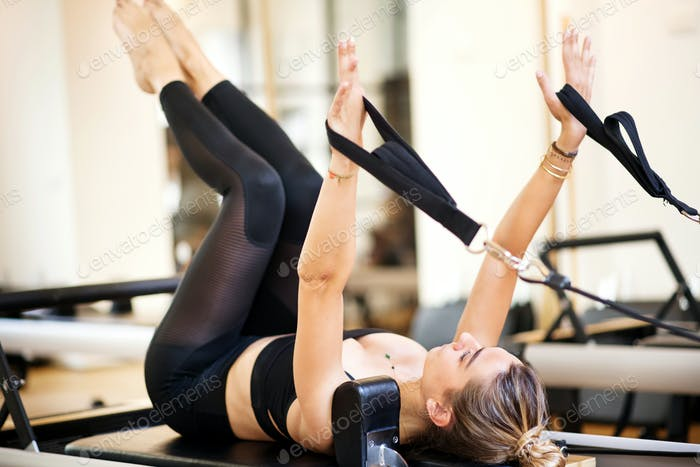 Woman lying on her back atop exercise bench