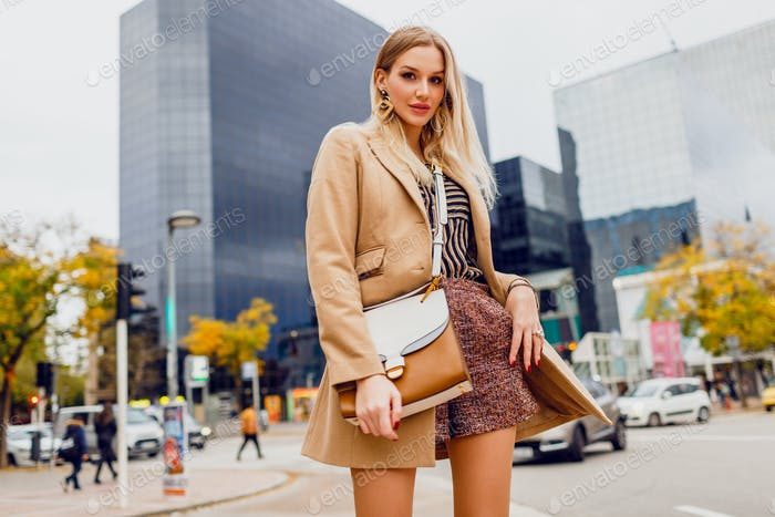 Fashion blond  wearing wool beige coat and stripped blouse.