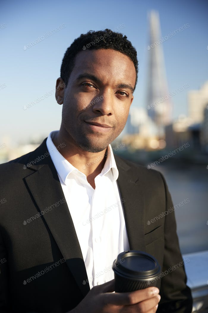 Young black businessman in smart casual clothing, smiling to camera