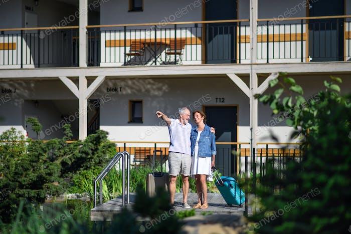 Senior couple with luggage outside apartment on holiday