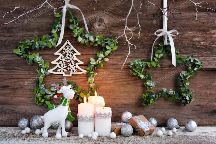 Christmas composition with candles, elk figurine and festive decorations