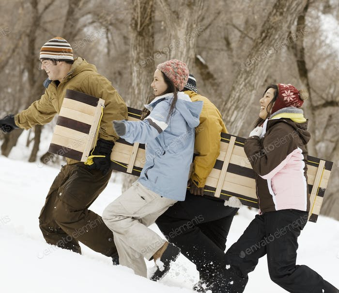 Four young people carrying a wooden sledge across the snow.