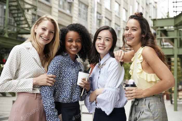 Vier weibliche Kollegen lächelnd zur Kamera draußen