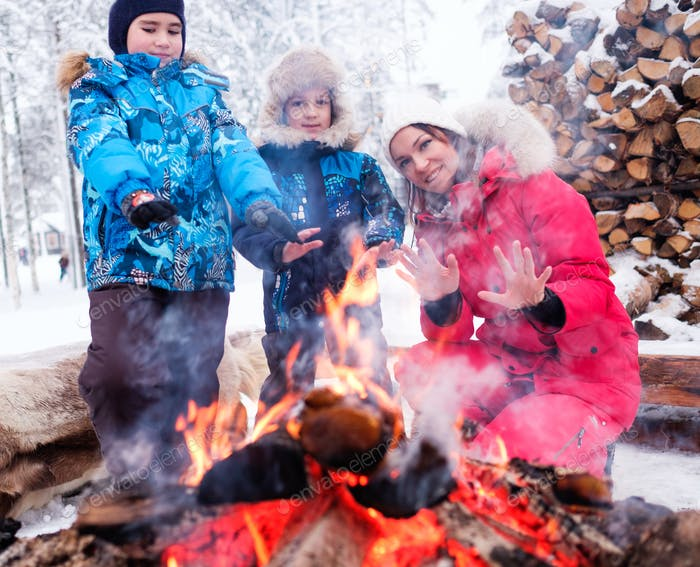 Family near bonfire in winter landscape