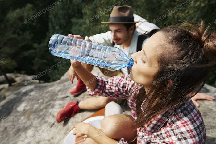 Female hiker drinking water in the mountains