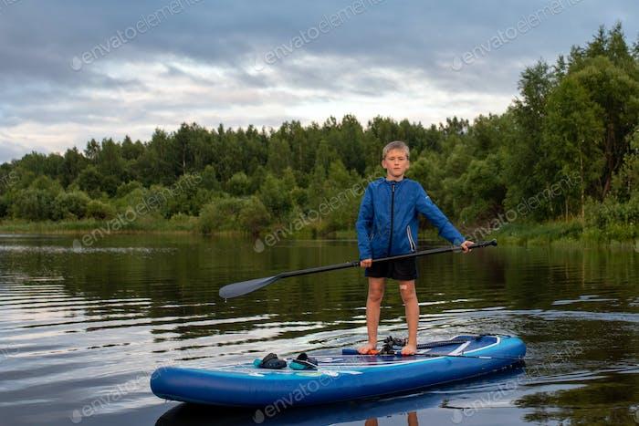 Junge auf dem Saft. Kinder surfen mit einem Paddel. Schwimmend.  Kind