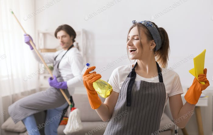 Playful Couple Having Fun While Cleaning Flat Together