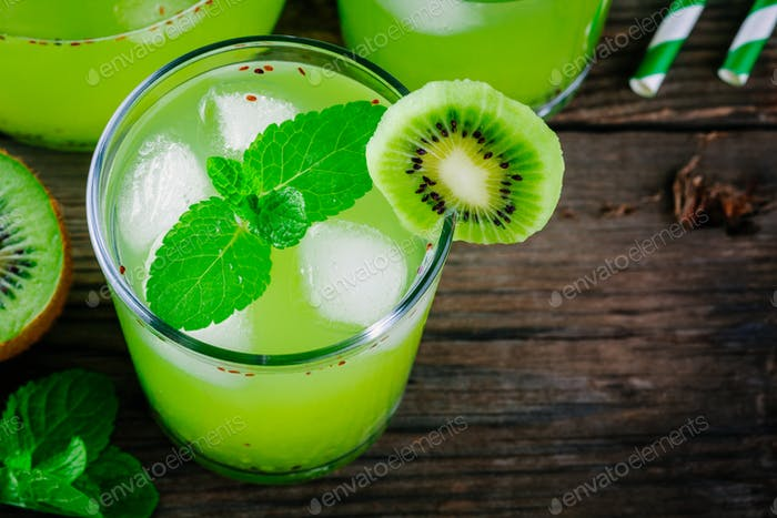 Ice drink with kiwi and mint in a glass on  wooden background.