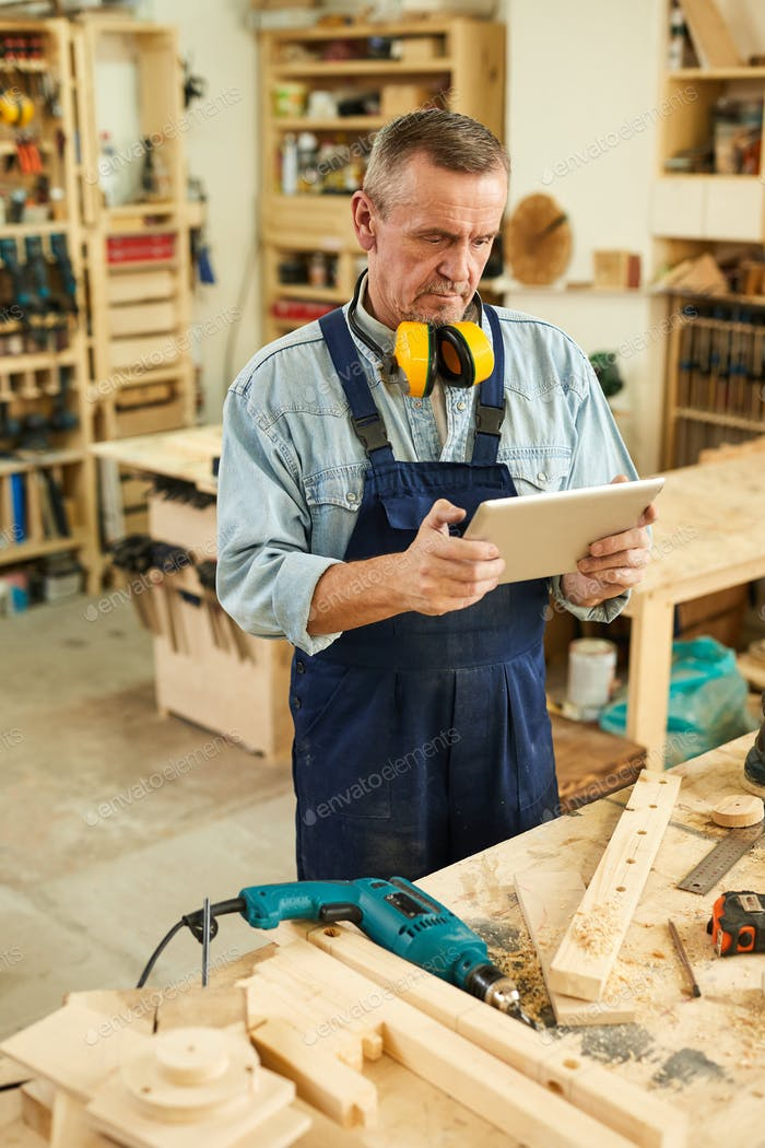 Senior Carpenter using Digital Tablet