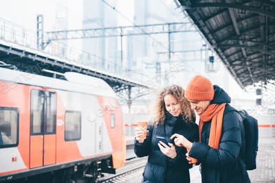 Couple checking info and waiting for the train at train station.