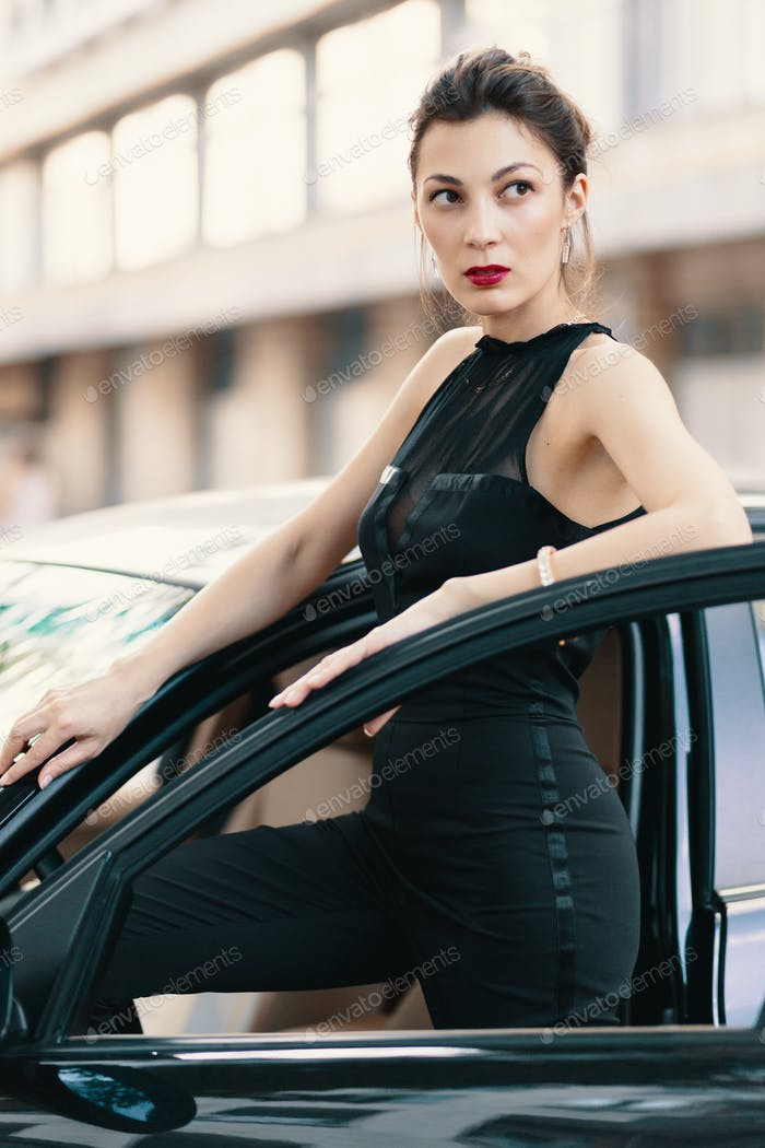 Sensual dangerous woman standing with a feline look in the door of a car ready to win the world