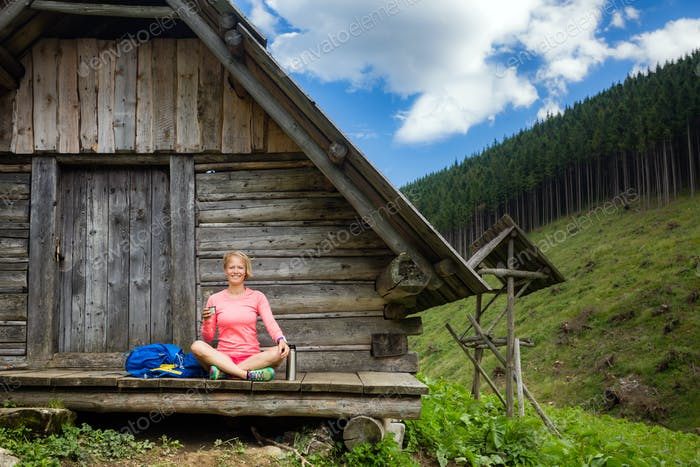 Woman drinking and camping in inspiring mountain landscape