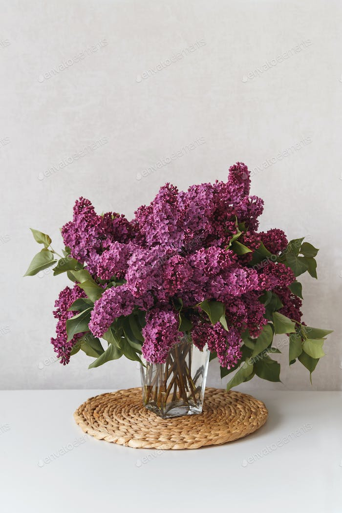 Vertical photo of beautiful lilac in glasses vase on white table.