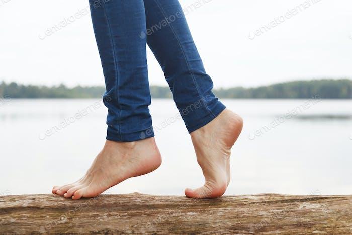 Womans feet walking on a log