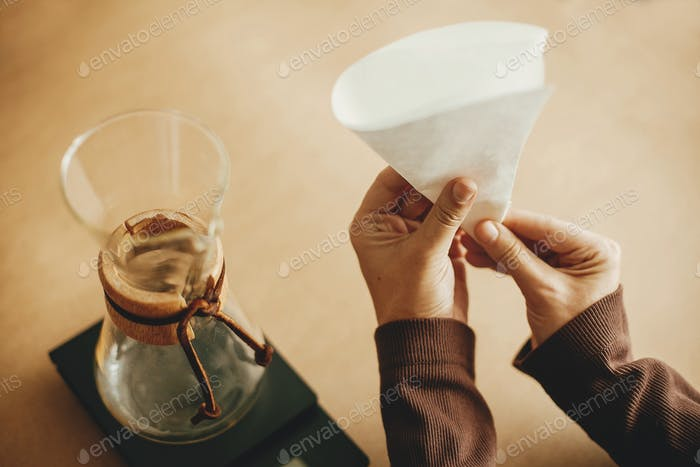 Hands folding paper filter for pour over and glass kettle on scale on brown background