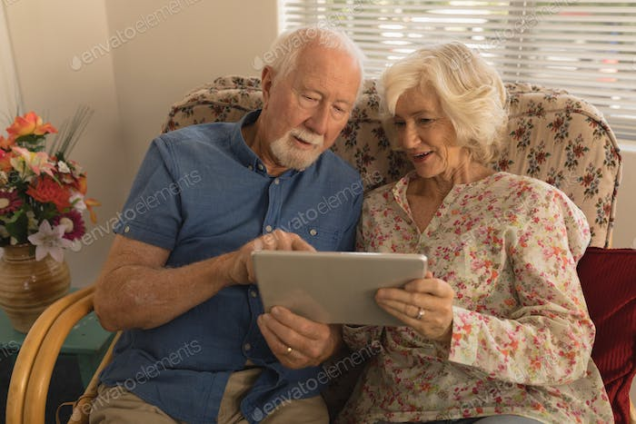 Front view of happy senior couple using digital tablet in living room at nursing home