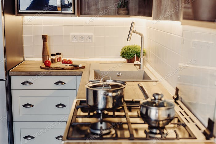 Luxury modern kitchen furniture in grey color and steel oven, sink, wooden tabletop