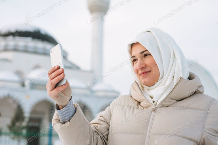Muslim woman in headscarf in light clothing takes selfie against the background of mosque
