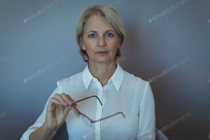 Portrait of businesswoman against wall