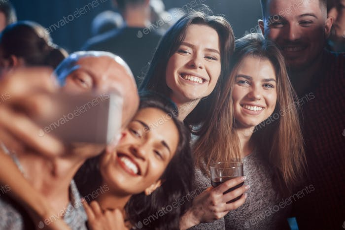 Photo for the memories. Friends taking selfie in beautiful nightclub. With drinks in the hands