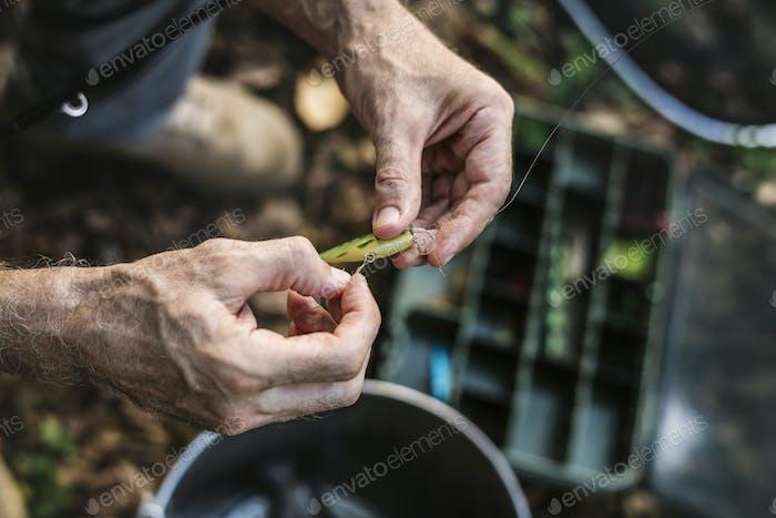 Primer plano de un pescador poniendo cebo