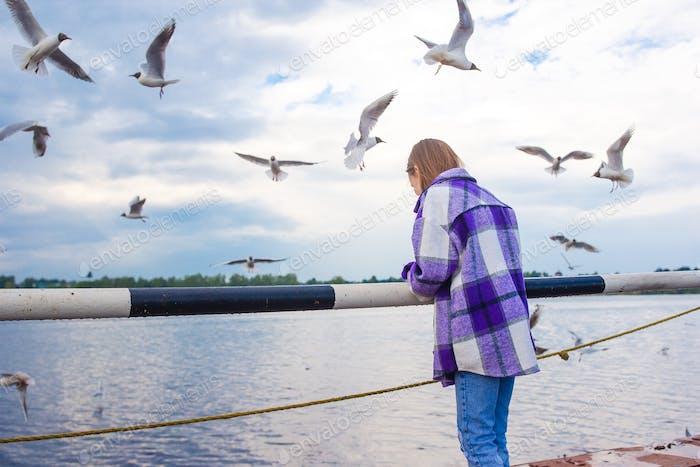 Cute little girl feed seagulls