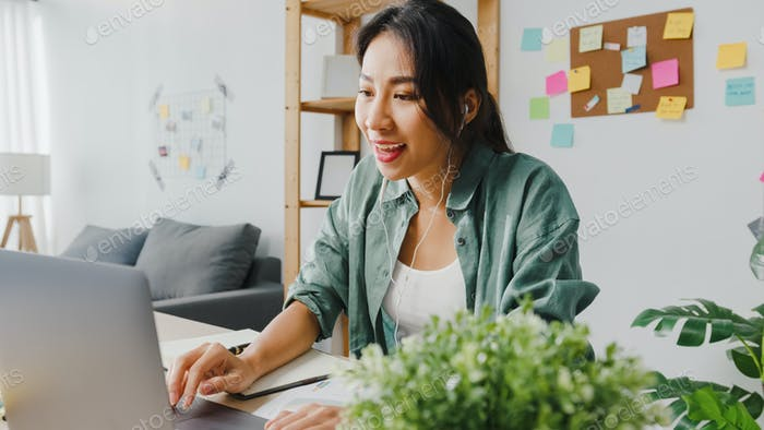Asia businesswoman using laptop talk to colleagues in video call while smart working from home.