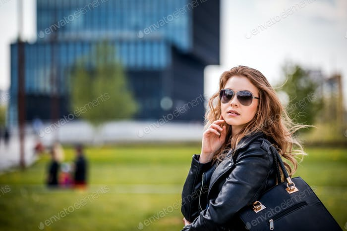 Young woman walking on modern green city area