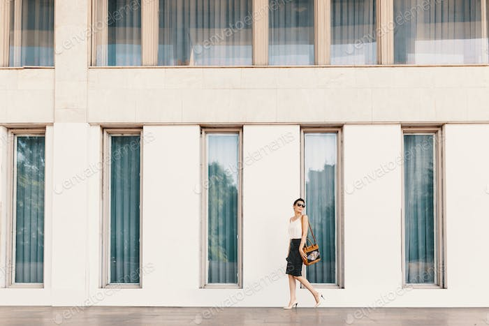 Fashionable tall business woman in sunglasses walking near a building with tall windows in the city