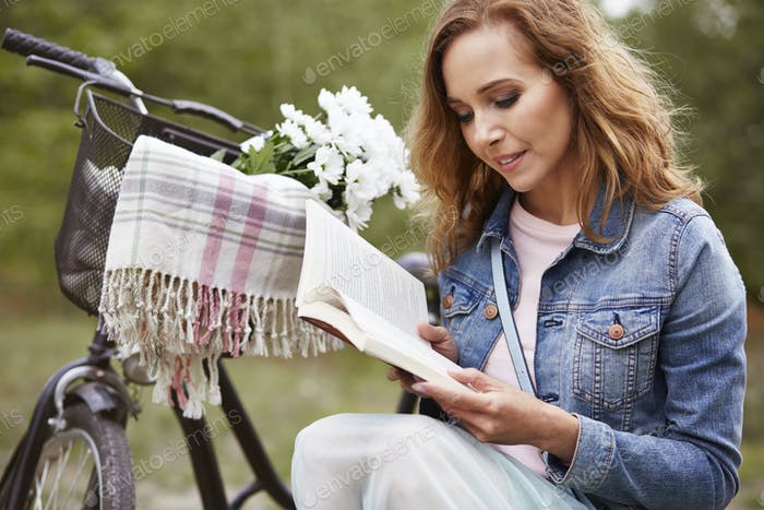 Woman reading book on the meadow