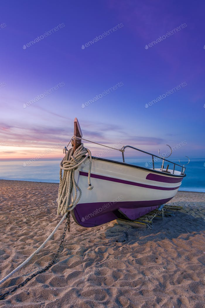 Fishing boat on sandy beach at nostalgic sunrise