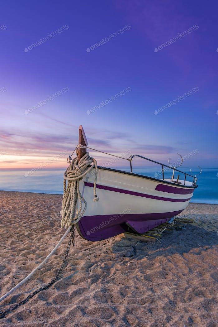Fischerboot am Sandstrand bei nostalgischem Sonnenaufgang