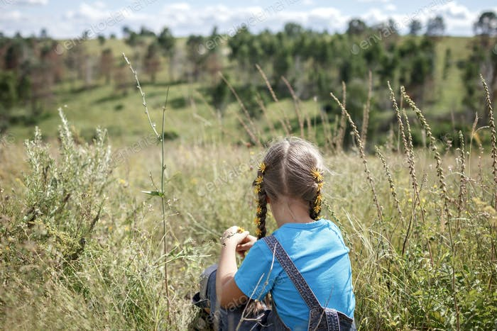 Girl with dandelions relaxing on nature, digital detox, escape, local travel and vacation