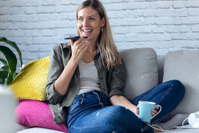 hübsche junge Frau im Gespräch auf dem Handy mit den Händen frei auf dem Sofa zu Hause.