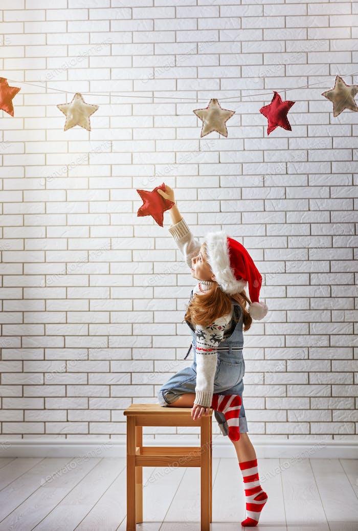 child hangs the stars