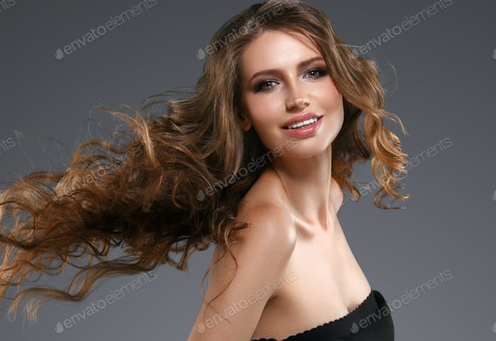 Female looking at camera  smiling on gray background. Beautiful hairstyle Youth Skin Care Concept.