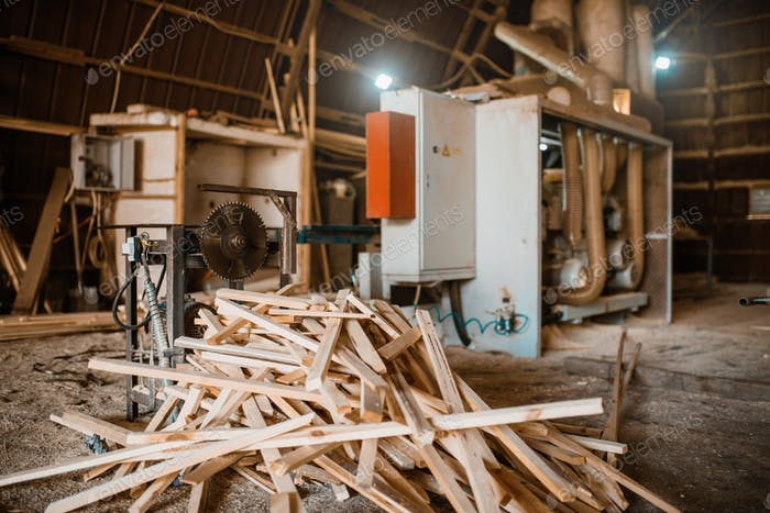 Stack of boards near woodworking machine, sawmill