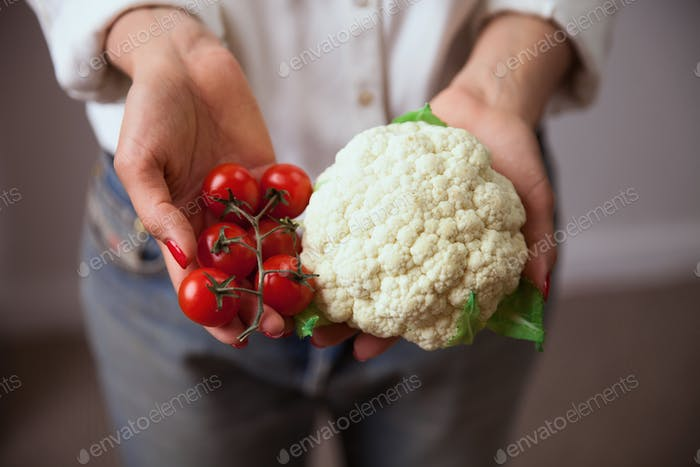 Young woman hands with cauliflower and cherry tomato