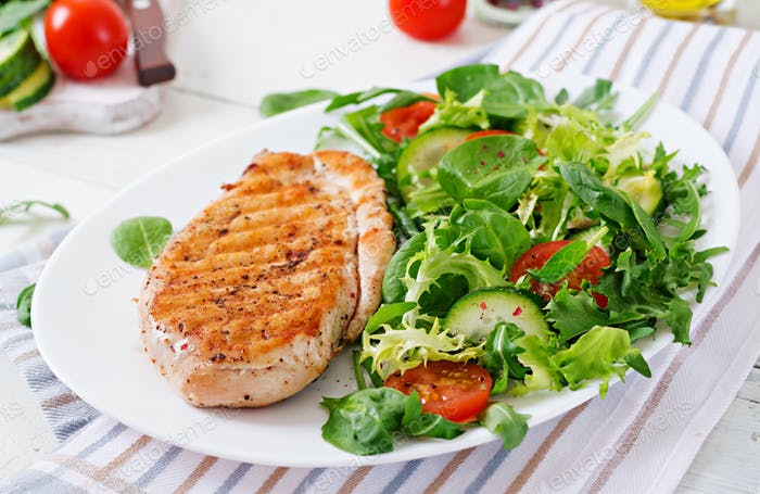 Grilled chicken breast and fresh vegetable salad - tomatoes, cucumbers and lettuce leaves.