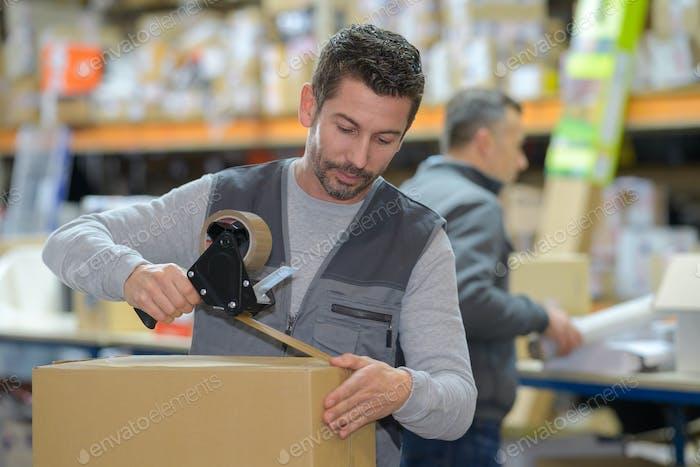 Hombre sosteniendo la máquina de embalaje y sellado de cajas de cartón